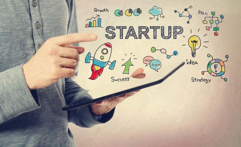 Young man pointing at Startup concept over a tablet
