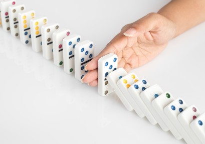 Hand stopping falling dominoes - domino effect