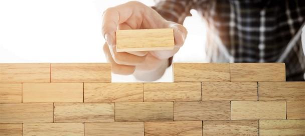 Hand of engineer playing a blocks wood tower game (jenga) on blu