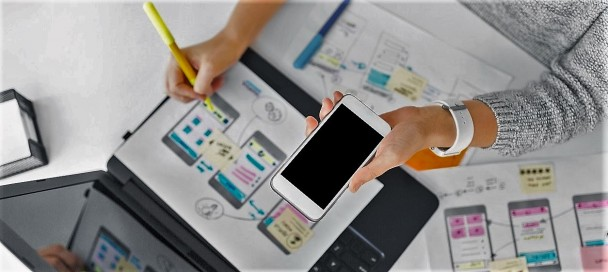 designer with smartphone working on user interface