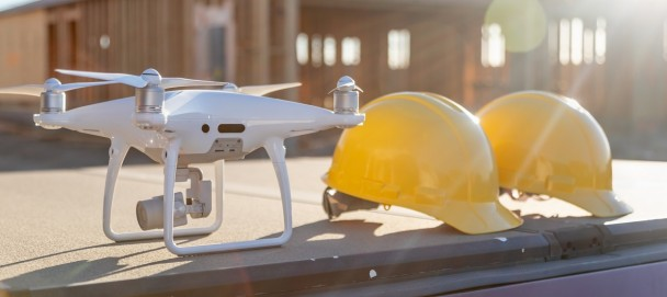 Drone Quadcopter Next to Hard Hat Helmets At Construction Site.