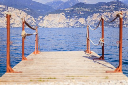 Summer holiday: Wooden dock pier over blue lake water, text spac